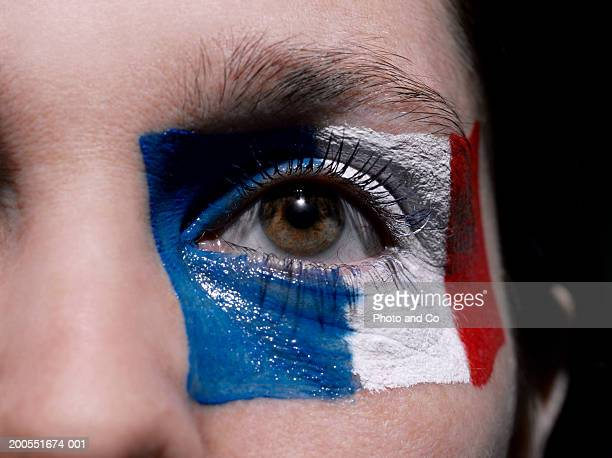Female rugby fan with French flag painted on face, close-up