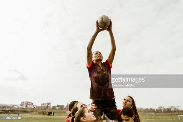 female rugby player catching a ball - rugby stock pictures, royalty-free photos & images