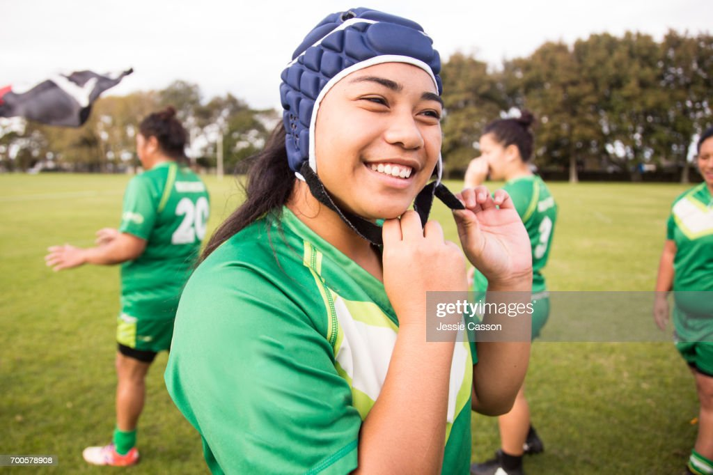 Female rugby player is smiling and putting on head gear : Stock Photo