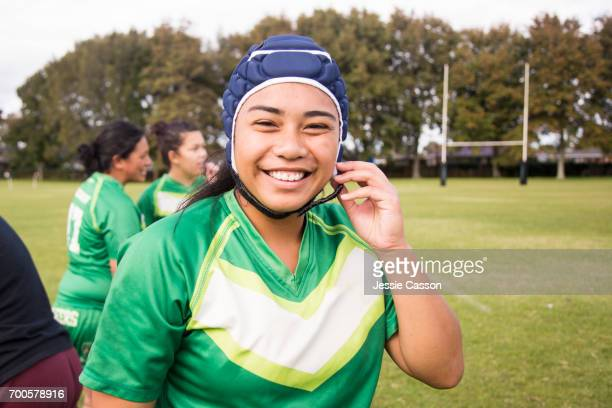 Female rugby player is smiling and putting on head gear