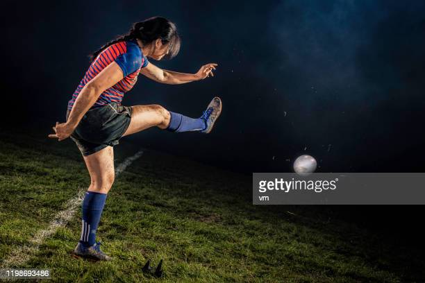 female rugby player kicking the ball - kicking stock pictures, royalty-free photos & images