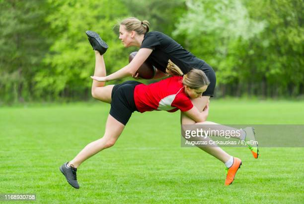 female rugby player tackling opponent on playing field - tackling stock pictures, royalty-free photos & images
