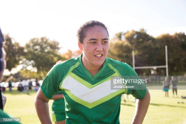 Female rugby player taking a break on field with hands on hip