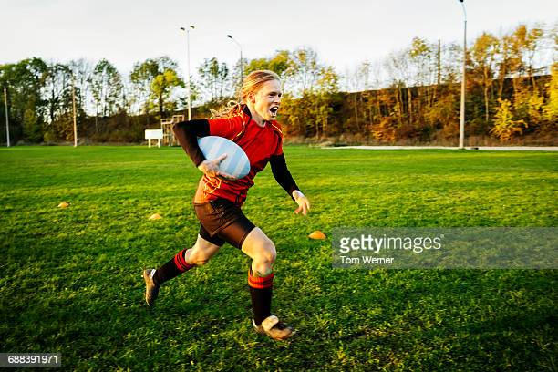 Female Rugby player with ball running on a field