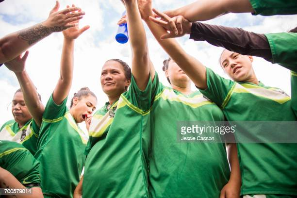 female rugby players bonding in circle with hands together before game - grittywomantrend stock photos and pictures