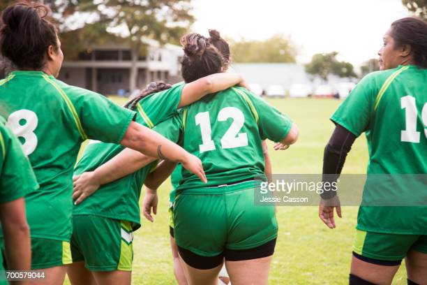 Female rugby players celebrate with arms around each other walking away with backs to camera
