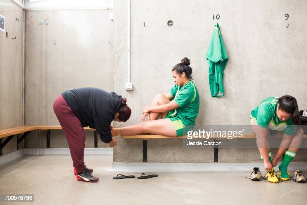 female rugby players in changing rooms getting ready for match, ankle bandage being applied - grittywomantrend stock photos and pictures