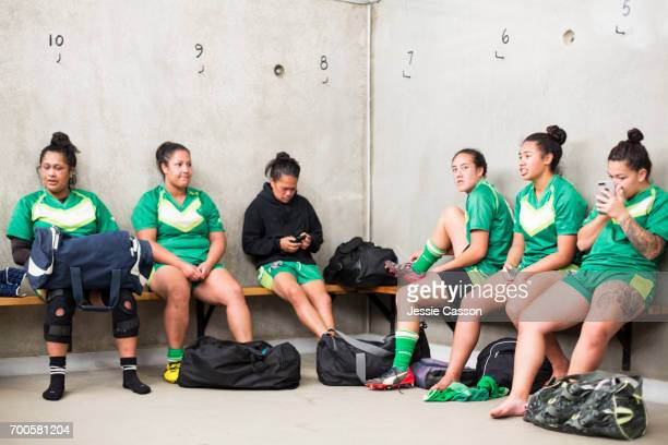 Female rugby players in changing rooms sitting on benches