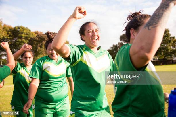 female rugby players on field celebrating after match - grittywomantrend stock photos and pictures