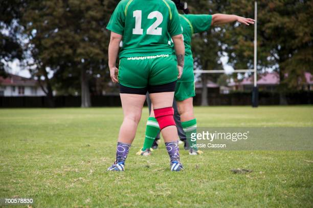 Female rugby players on field standing with back to camera