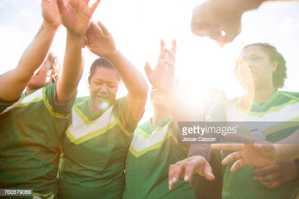 female rugby players put hands together in bonding exersise before match - grittywomantrend stock photos and pictures