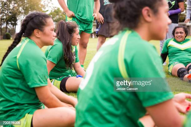 Female rugby players sit at side of pitch having team talk