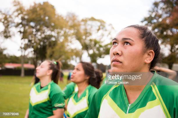 female rugby players stand on field looking up - grittywomantrend stock photos and pictures