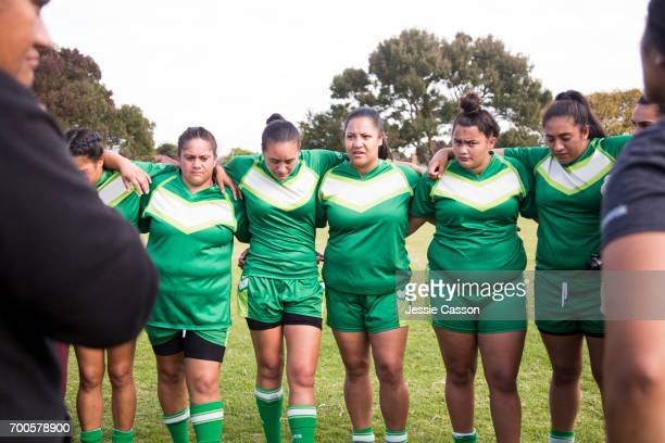 Female rugby players tackling in action playing a rugby match