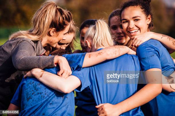 female rugby players together in a huddle - squadra sportiva foto e immagini stock