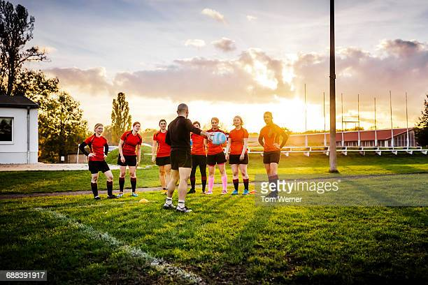 Female rugby team briefing with trainer