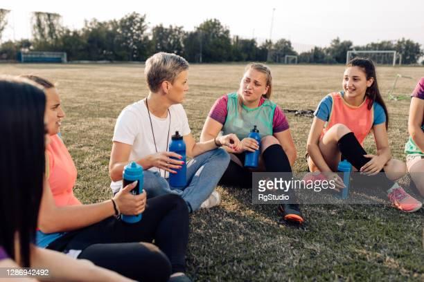 equipo femenino de rugby enfriándose y charlando con su entrenador - rugby union fotografías e imágenes de stock