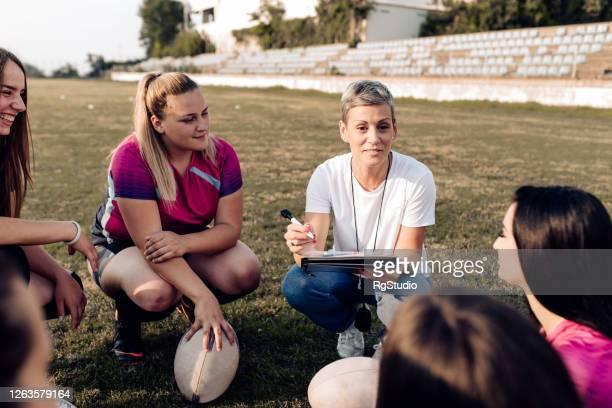 équipe féminine de rugby faisant une stratégie pour leur jeu - rugby union photos et images de collection
