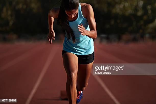 female runner accelerating out of start block - endurance photos et images de collection