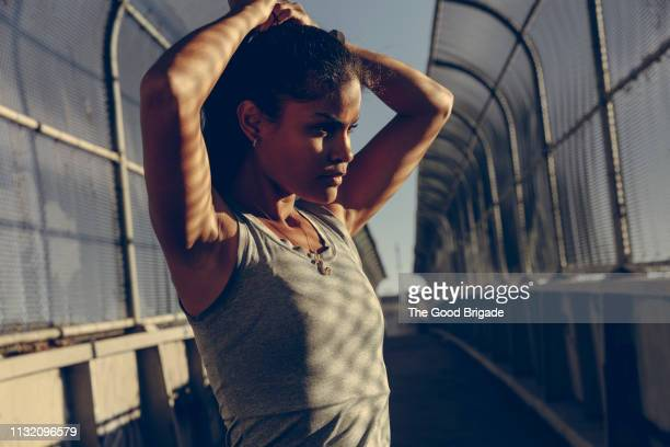 female runner adjusting ponytail before run - ponytail stock pictures, royalty-free photos & images
