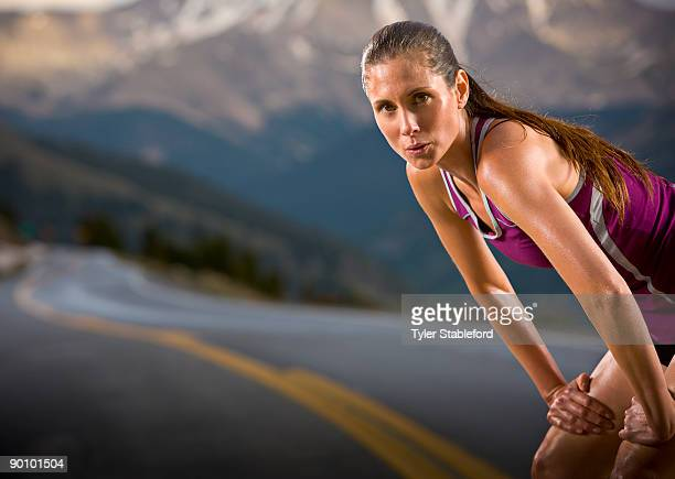A female runner catches her breath on curvy road.