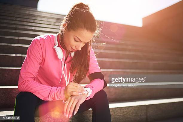 Female runner checking info on smart watch
