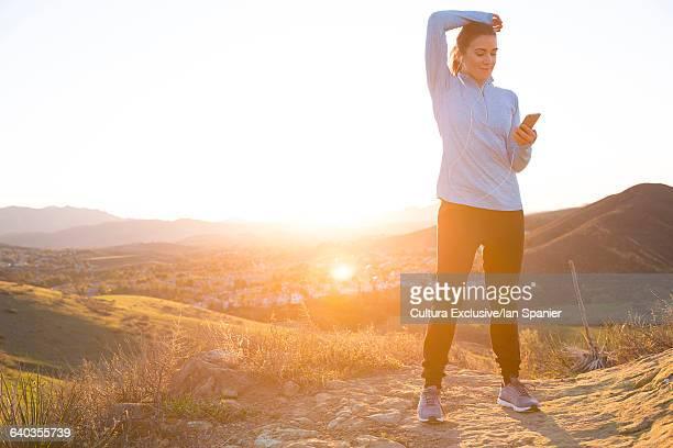 female runner choosing earphone music on mountain trail at sunset - thousand oaks - fotografias e filmes do acervo