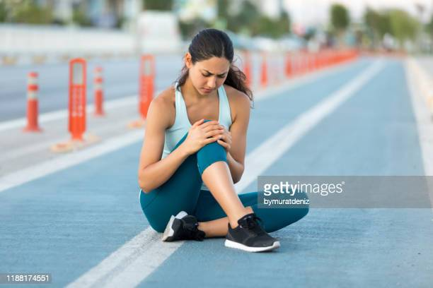 female runner clutching injured knee - down on one knee stock pictures, royalty-free photos & images