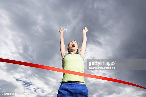 Female runner crossing finishing line (low angle view)