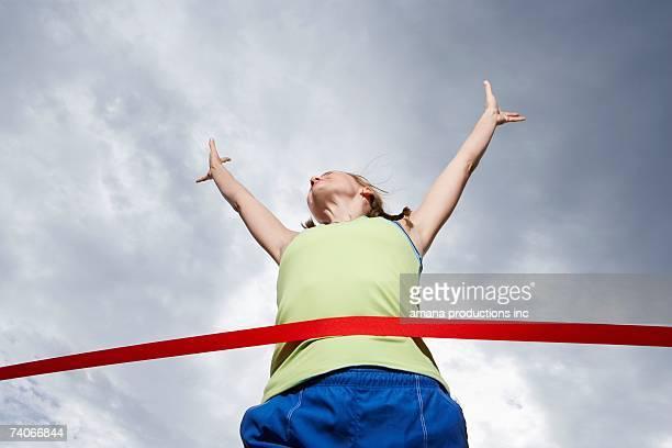 female runner crossing finishing line (low angle view) - cruzar fotografías e imágenes de stock