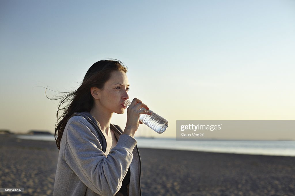 Female runner drinking water at the beach : Stockfoto