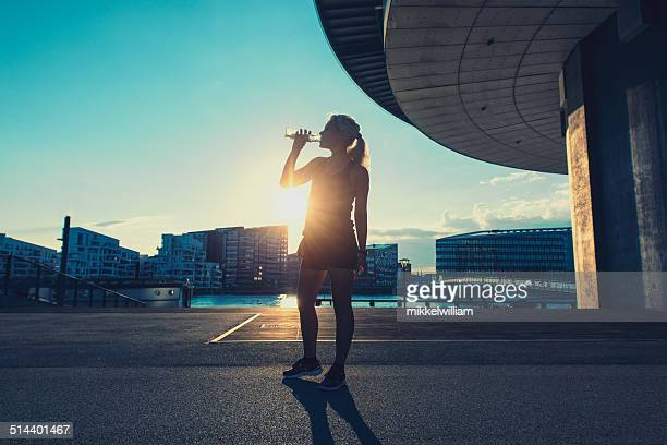 Female runner drinks water after a run in the city