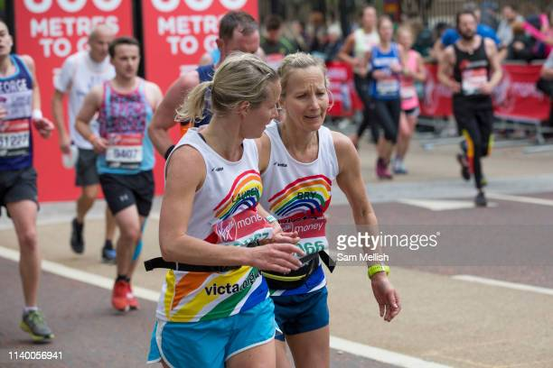 A female runner encourages a teammate during the finale 600 metres of The Virgin London Marathon at Birdcage Walk on 28th April 2019 in London in the...