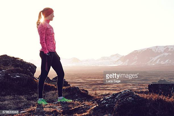 Female runner gazes across early morning landscape