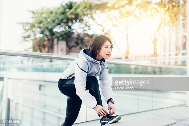 Female runner getting read for a run in city