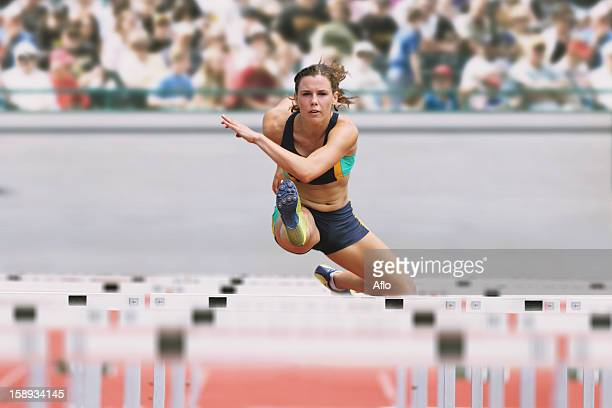 female runner hurdling - hurdling stock photos and pictures