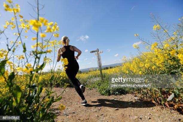 Female runner in rapeseed field