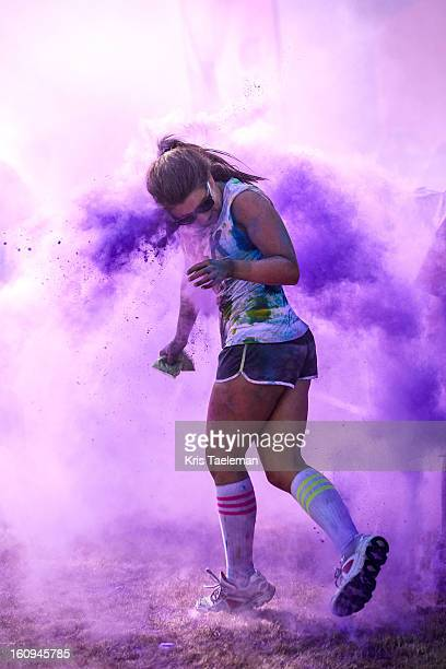 "Female runner is being bombarded with purple cornstarch at a special race called ""Color me rad"" where participants get covered with paint while..."