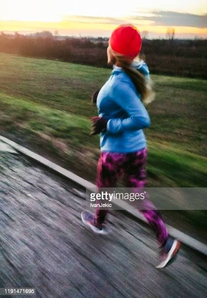female runner jogging on the road at sunset - ivanjekic stock pictures, royalty-free photos & images