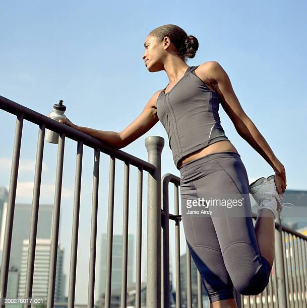 Female runner leaning on railing, stretching leg