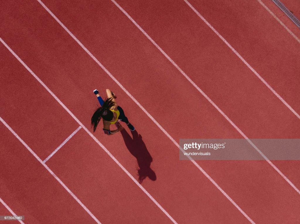 Vrouwelijke runner luisteren naar muziek en sport track waarop : Stockfoto