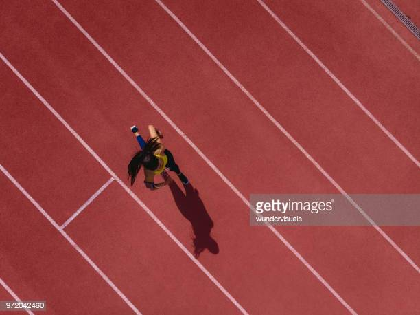 female runner listening to music and running on sports track - atleta imagens e fotografias de stock