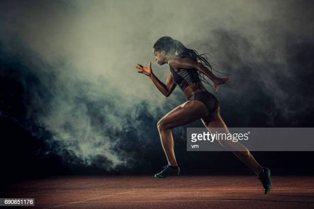 female runner of african descent in mid-air - athletics stock photos and pictures