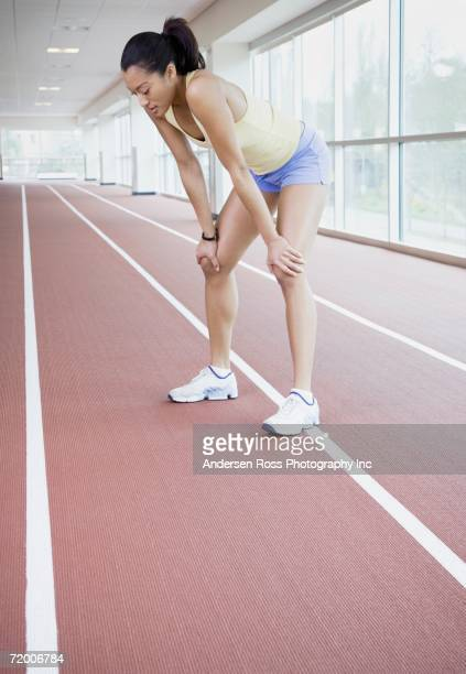 female runner on indoor track - bend over woman stock pictures, royalty-free photos & images
