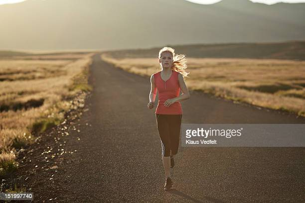 Female runner on long solitary road
