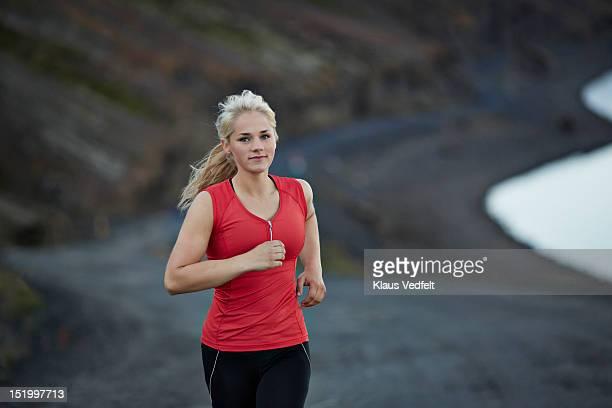 Female runner on mountain road, lake in background