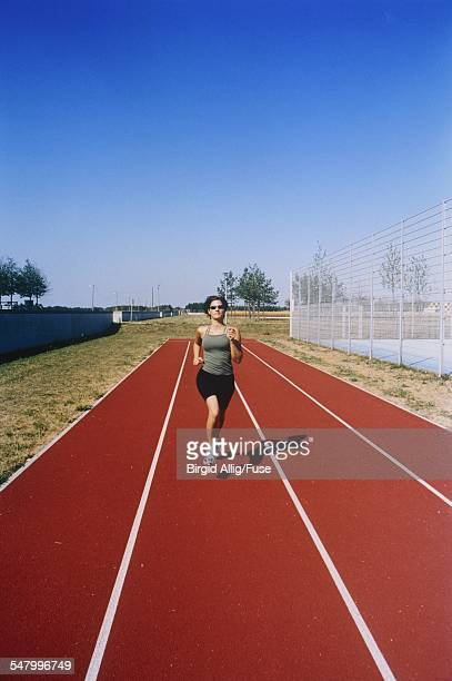 female runner on tartan track - center athlete stock pictures, royalty-free photos & images