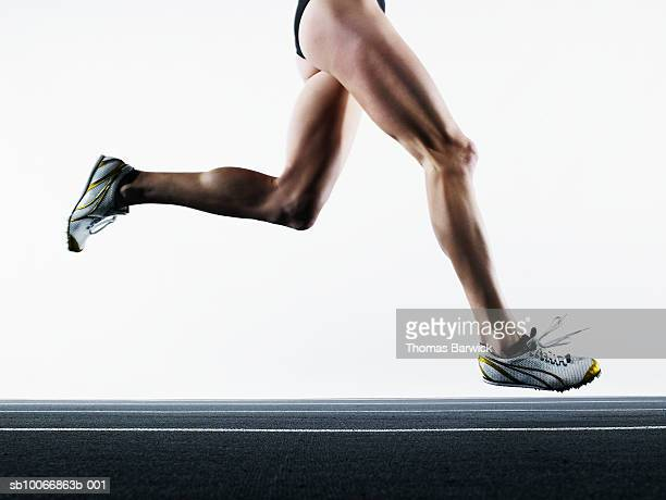 female runner on track, low section - leg stock pictures, royalty-free photos & images