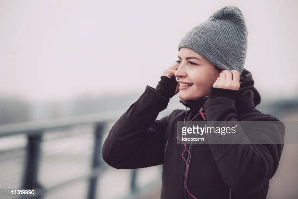 female runner putting on earphones - winter coat stock pictures, royalty-free photos & images