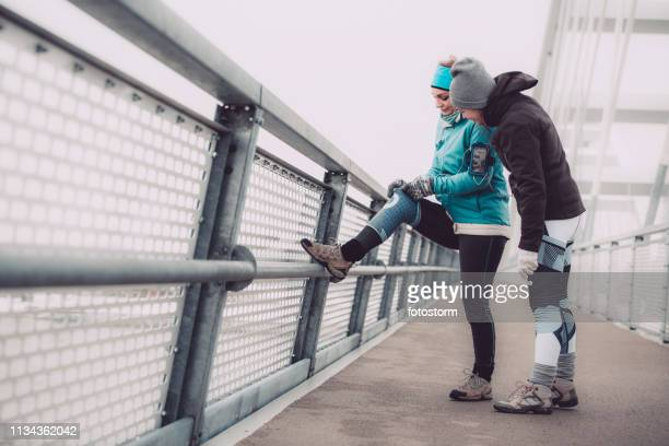 female runner putting on knee sleeves - long sleeved stock pictures, royalty-free photos & images